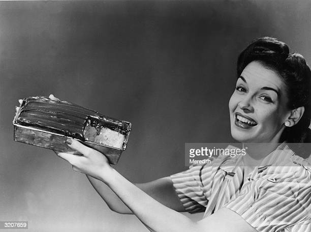 Woman cheerfully holds up a cake in a baking pan with a slice cut out