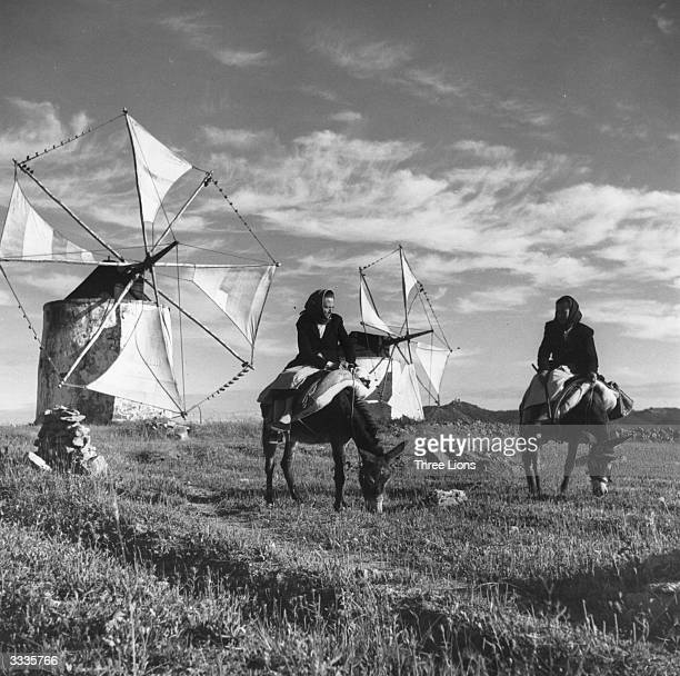 Women riding small donkeys or burros in front of octagonalshaped windmills in Obidos Portugal