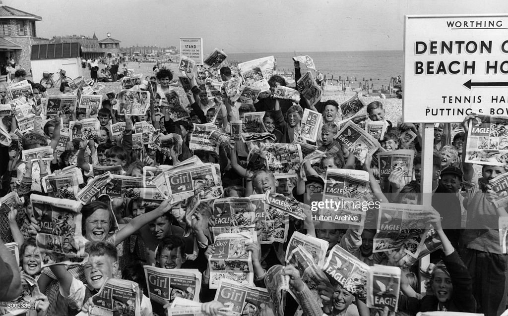 Young holidaymakers in Worthing, Sussex, waving copies of the Eagle and Girl comics.