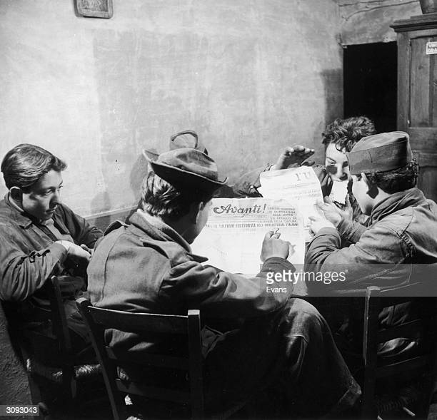 Young Italian men having lunch in a cafe in Rome and reading the communist paper 'Unita' and the socialist 'Avanti'