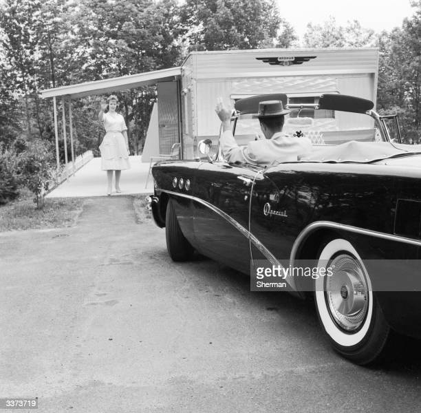A wife waves goodbye to her husband from the patio of their mobile home in America as he drives off to work