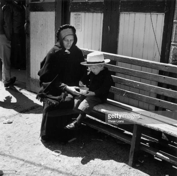 A young Amish boy gets a treat of icecream from his mother during a trip into town