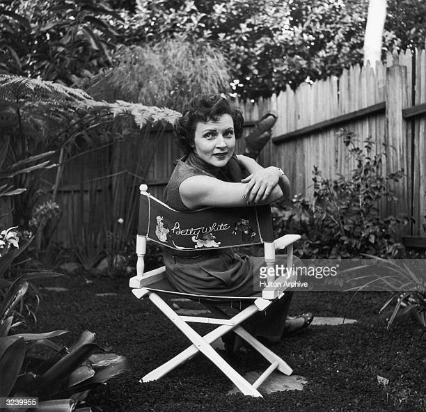 American actor Betty White sits in a canvas chair with her name written on the back looking over her shoulder in a backyard garden