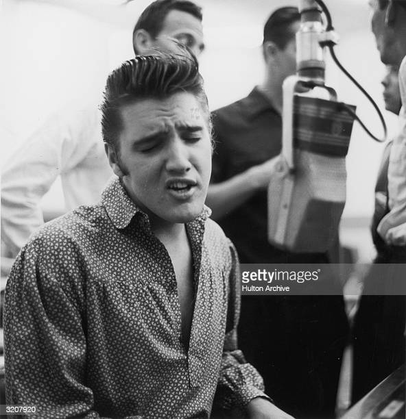American Rock musician and actor Elvis Presley singing and playing the piano during a recording session for RCA
