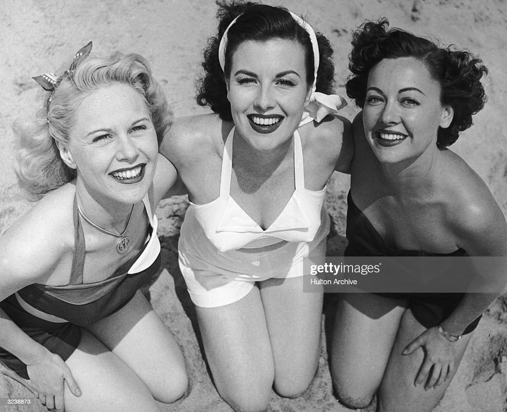 High angle view of three women wearing swimsuits kneeling arm-in-arm on a sandy beach, smiling at the camera.
