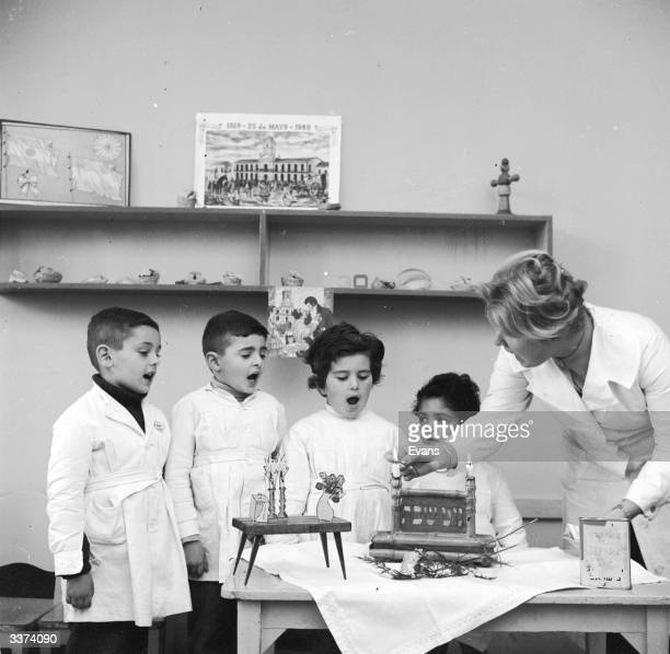 Schoolchildren at the 'Scholem Aleijen School' in Buenos Aires observe the lighting of the candles on the Jewish Sabbath