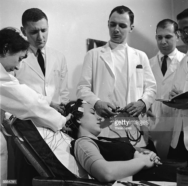 Students at the New York Medical College look on as electrodes are attached to the patient's head for an electroencephalogram reading