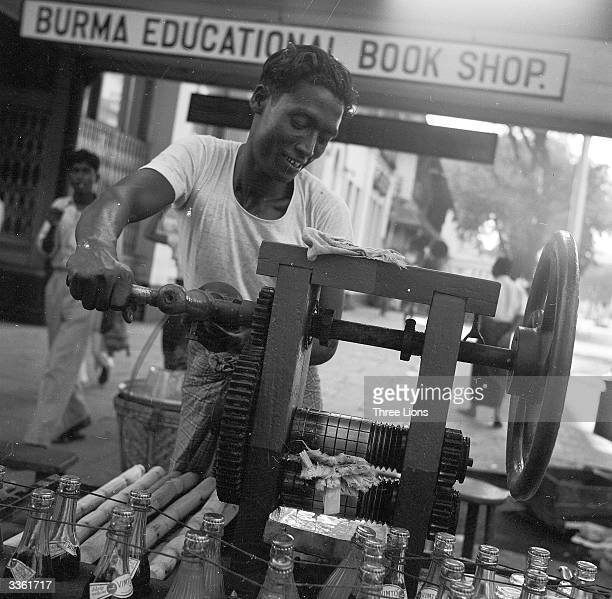 The juice of crushed sugarcane is mixed with icewater to provide refreshment on the streets of Rangoon Burma