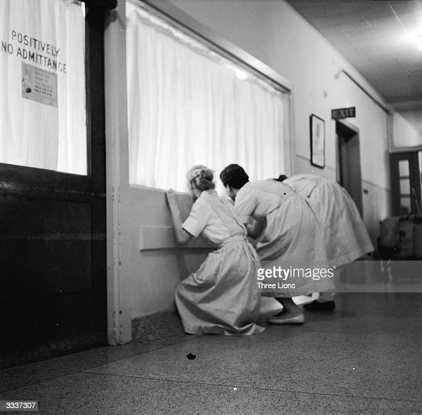 Woman sneaking a look at new arrivals in a hospital nursery