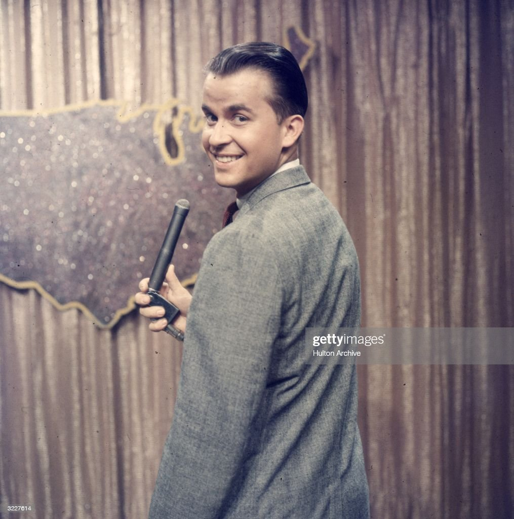 American TV host and producer Dick Clark looks over his shoulder while holding a microphone on the set of the television series 'American Bandstand'