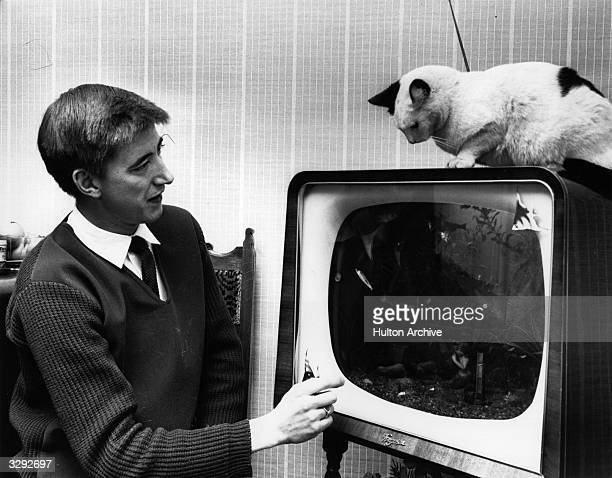 A man sits in front of the television set he turned into a fishtank while his cat looks on tempted by the tropical fish swimming behind the screen