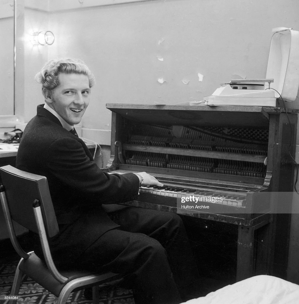 American rock n' roll singer and pianist Jerry Lee Lewis smiles over his shoulder while playing the piano in a dressing room.