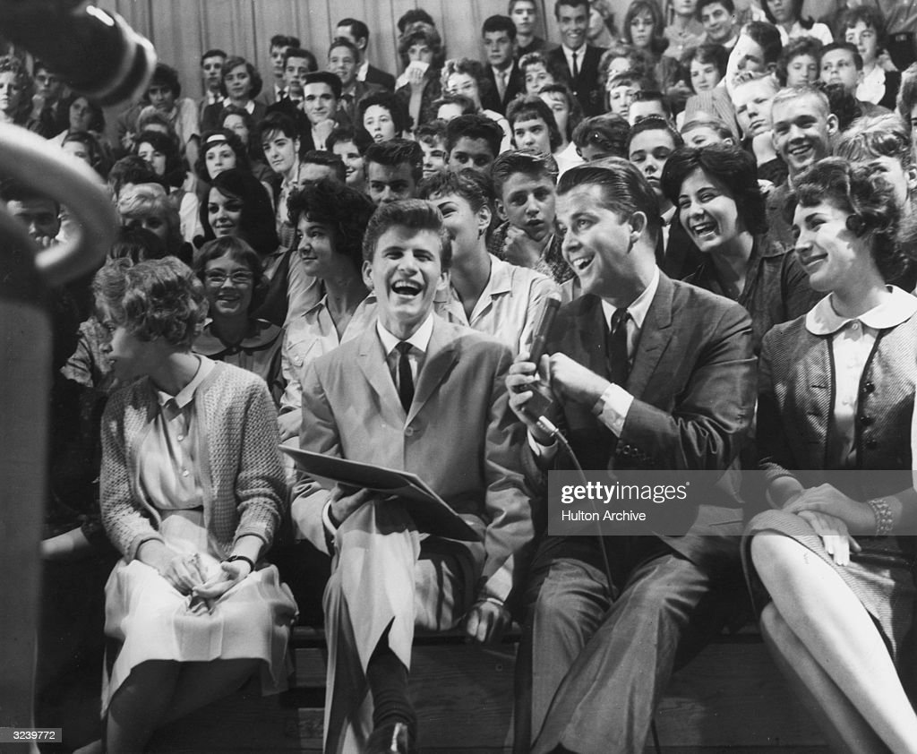 American singer and musician Bobby Rydell sits next to American television host Dick Clark in the audience of the television show 'American Bandstand'