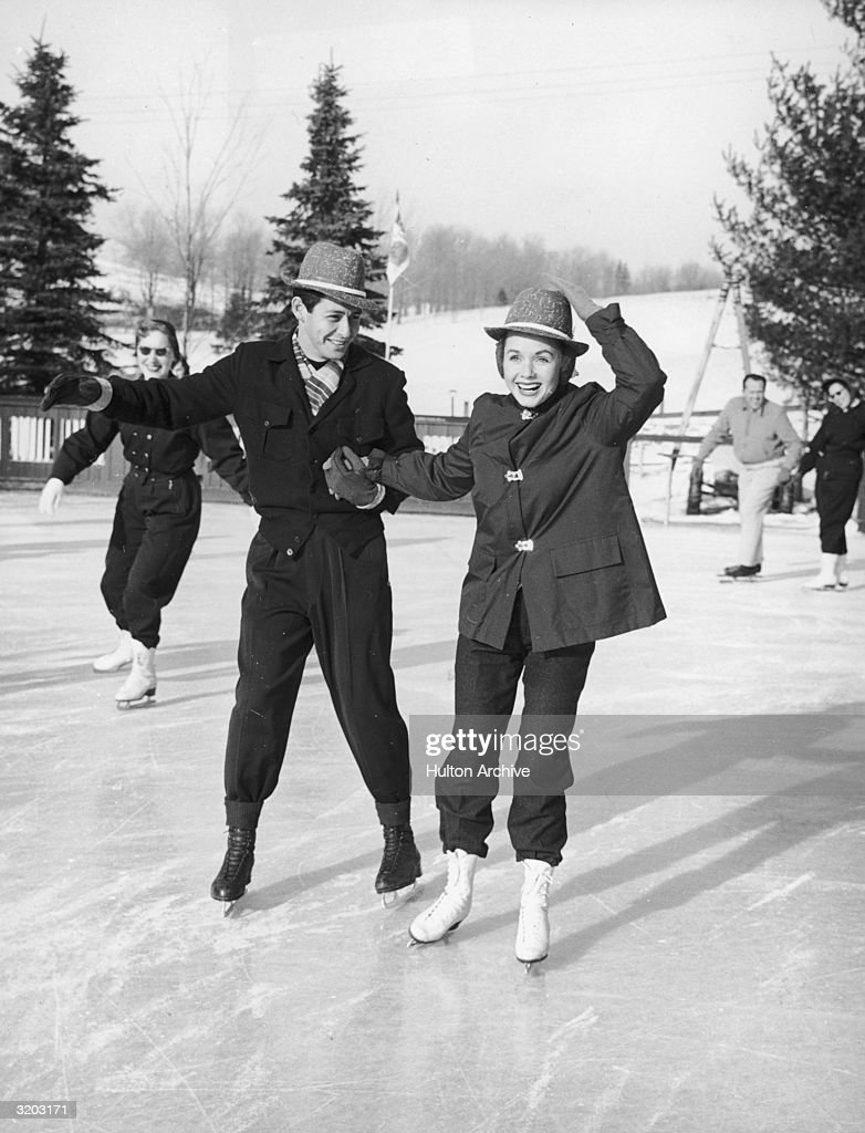 Full-length image of married American singer/actors Eddie Fisher and Debbie Reynolds ice skating on an outdoor rink. Both wear matching hats.