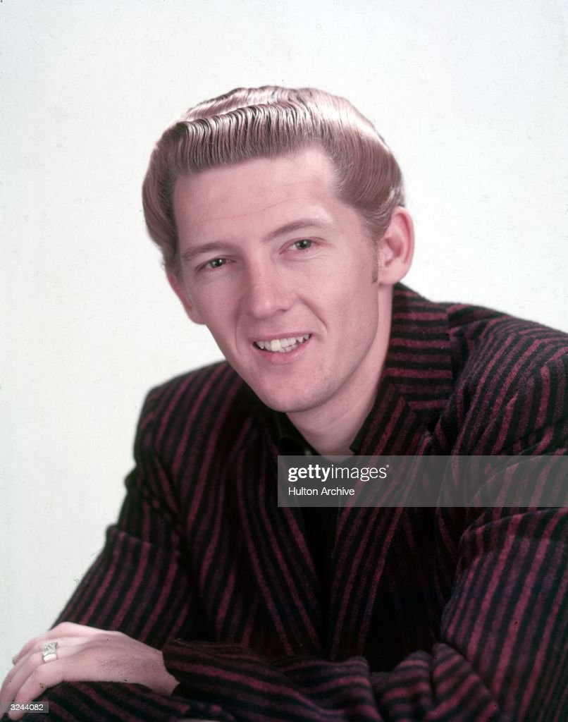 Promotional studio headshot portrait of American rock n' roll singer and pianist Jerry Lee Lewis wearing a striped blazer.