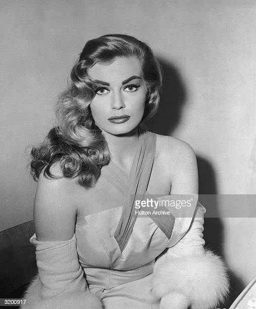 Seated portrait of Swedishborn actor Anita Ekberg wearing a dress with crisscrossed straps and a cardigan with fur trim 1950s Ekberg looks as she...
