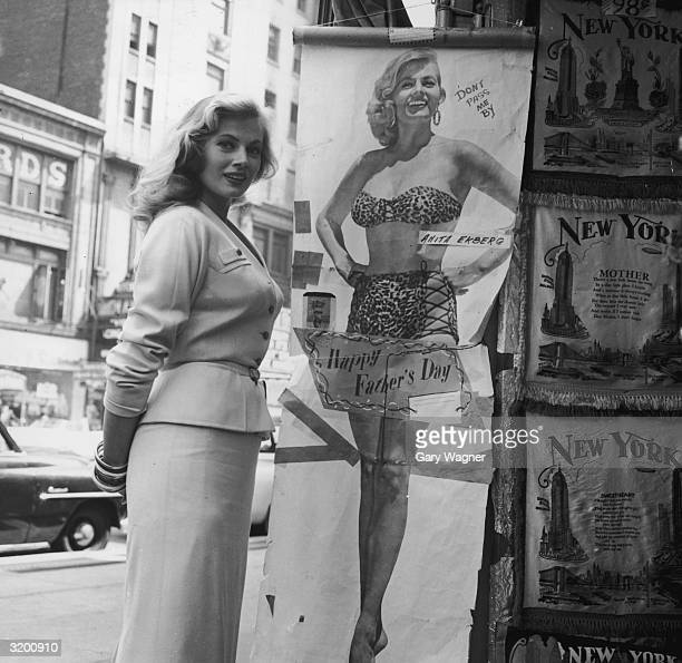 Swedishborn actor Anita Ekberg wearing a skirt suit poses next to a fulllength poster of herself wearing a twopiece leopard print swimsuit which...