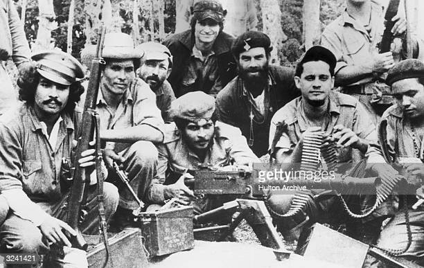 A group photo of Cuban citizen militia displaying weapons captured from dictator Fulgencio Batista's army in Fidel Castro's '26 of July Movement'...