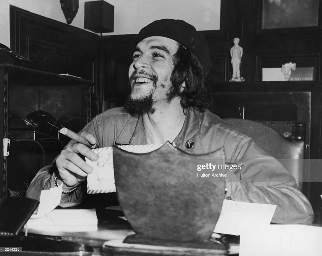 Argentinian-born revolutionary Ernesto 'Che' Guevara (1928 - 1967), Cuban minister of industry, sits at a desk and smokes a cigar.