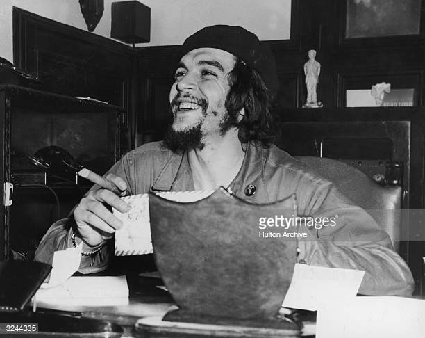 Argentinianborn revolutionary Ernesto 'Che' Guevara Cuban minister of industry sits at a desk and smokes a cigar