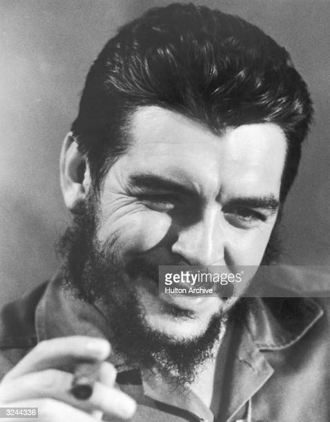 Closeup of Ernesto 'Che' Guevara Cuban minister of finance smoking a cigar in military fatigues