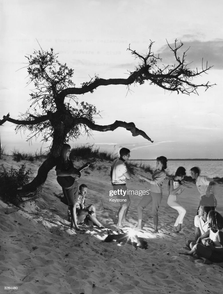 A group of young people enjoying themselves at a beach party on the white sands of the Miracle Strip, a stretch from Pensacola to Panama City, Florida.