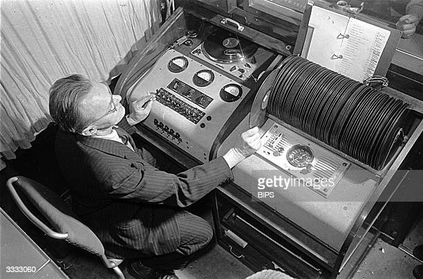 A man operating a record player in a radio studio