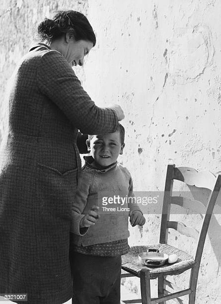 A mother removes lice from the scalp of her son in the street of Sicilian slum area The egg on the chair is a luxury in the undernourishing diets of...