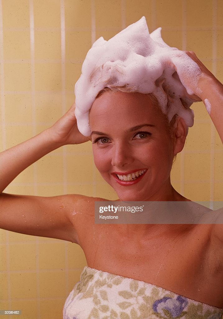 A woman lathers shampoo into her hair