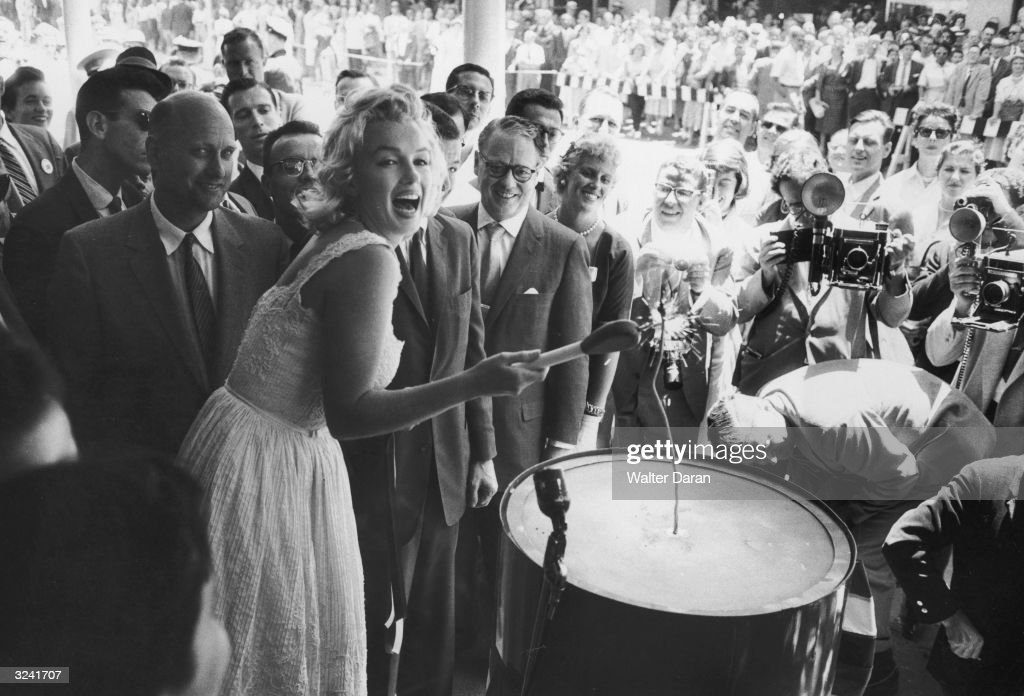 American actor Marilyn Monroe uses an outsize match to light a large firecracker during the ribbon cutting ceremony at the TimeLife Building in New...
