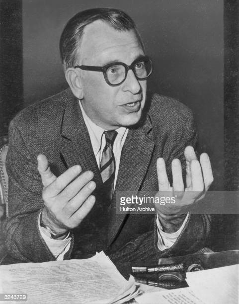 American architect Eero Saarinen wearing eyeglasses gestures with his hands while talking in front of a desk