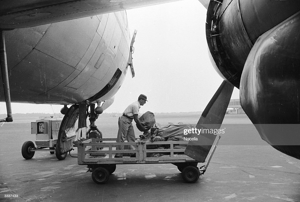 An airline employee loading mail bags onto a wagon at Philadelphia airport, Pennsylvania.