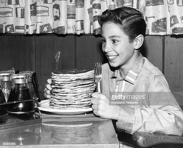 Child actor Johnny Crawford looks forward to eating a pile of pancakes in an International House of Pancakes a chain of eateries in the USA started...