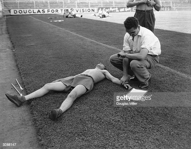 Dr Alan Bass checks the pulse of Tony Luckett of Crystal Palace football team during stamina tests at Selhurst Park