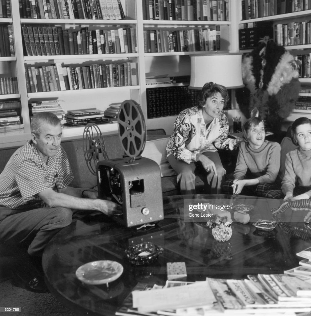American actor James Stewart (1908-1997) operates a film projector while his wife, Gloria, and their twin daughters, Judy and Kelly, watch an unseen movie screen in the living room of their home, California.
