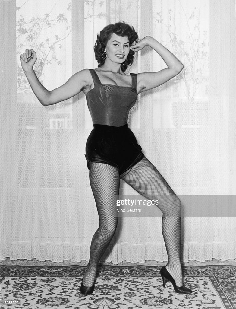 Fulllength view of Italian actor Sophia Loren posing in a cabaret costume with fishnet stockings and high heels in front of a window
