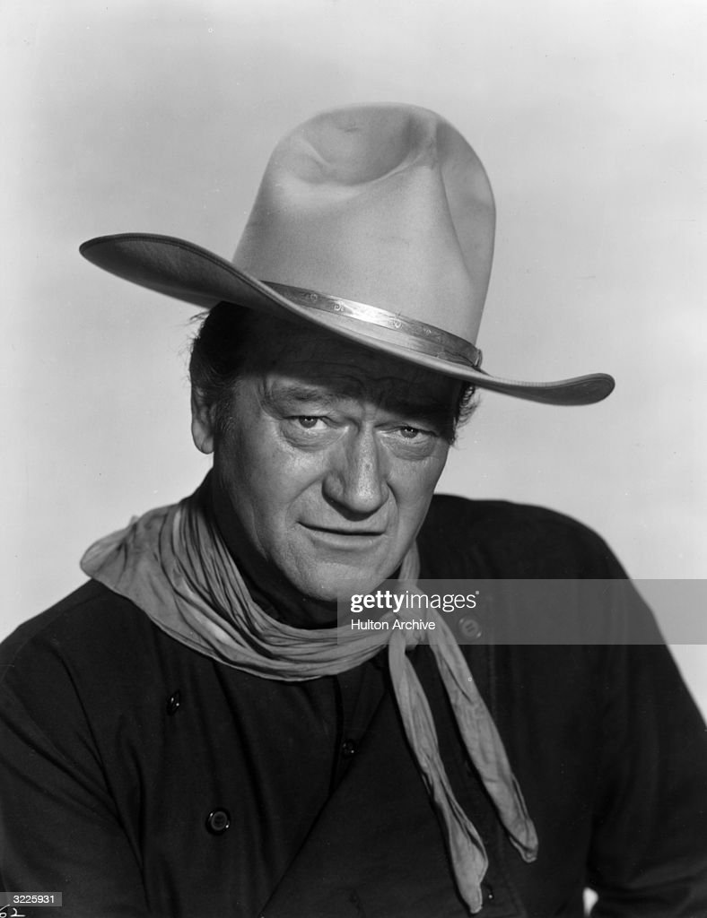 Headshot portrait of American actor <a gi-track='captionPersonalityLinkClicked' href=/galleries/search?phrase=John+Wayne&family=editorial&specificpeople=69997 ng-click='$event.stopPropagation()'>John Wayne</a> (1907 - 1979) dressed as a cowboy with a bandana around his neck and a white cowboy hat on his head.