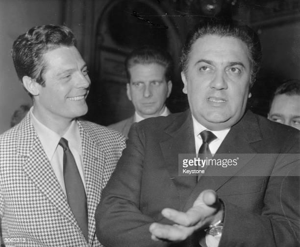 Italian filmmaker Federico Fellini with the actor Marcello Mastroianni during a press conference in Paris promoting the film 'La Dolce Vita'