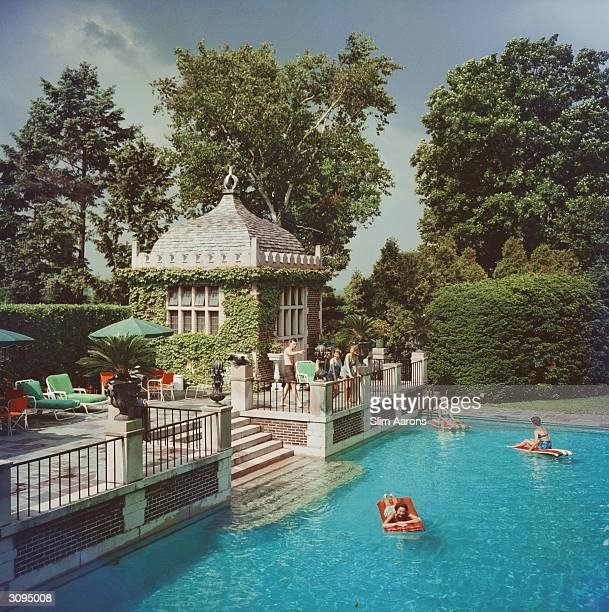 Mrs A Watson Armour III with friends and family enjoying the pool on their estate at Lake Forest Illinois A Wonderful Time Slim Aarons