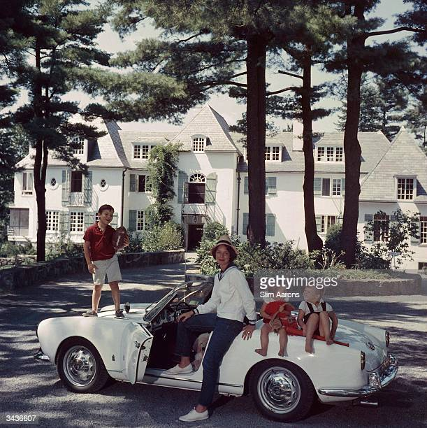Mrs Henry Cabot Jnr with her children Henry Bromfield Cabot III Camilla Foote Cabot and Andrew Hull Cabot sitting on a car in the driveway of their...