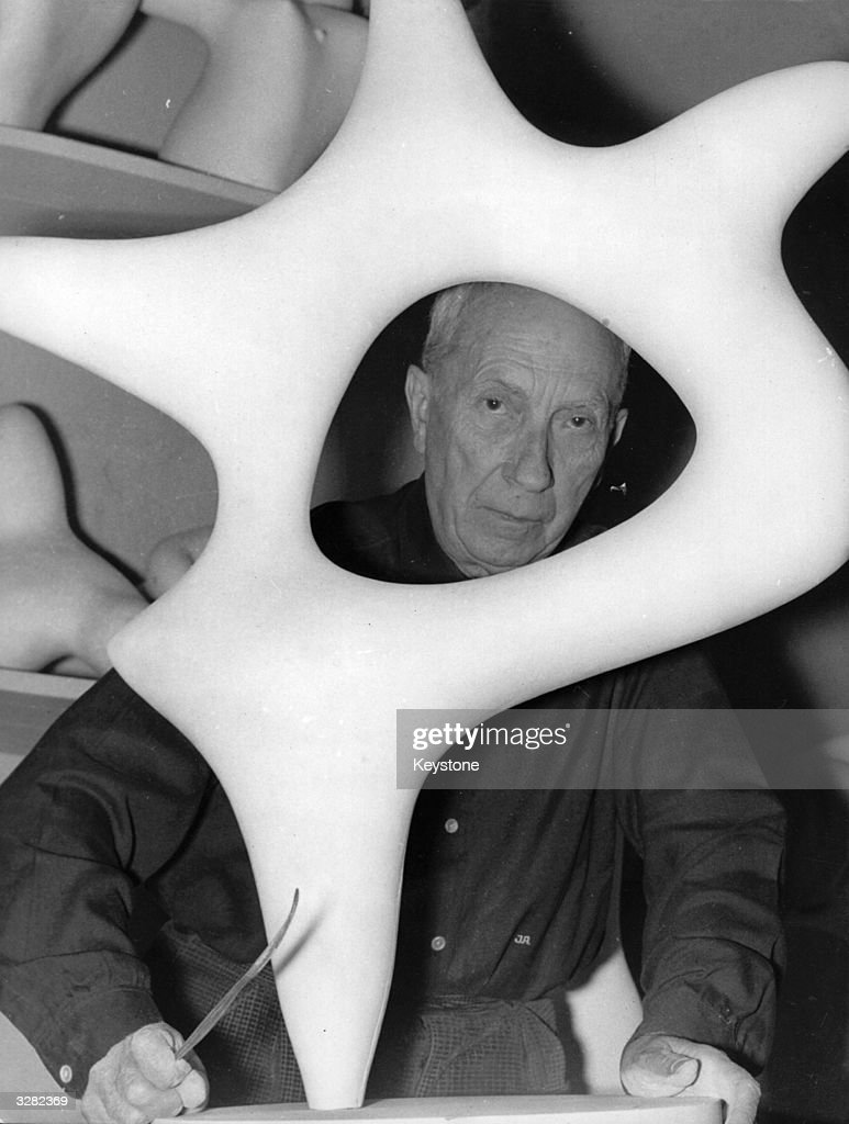 Painter, poet and sculptor Jean Arp (1887 - 1966) with one of his typical curved pieces.