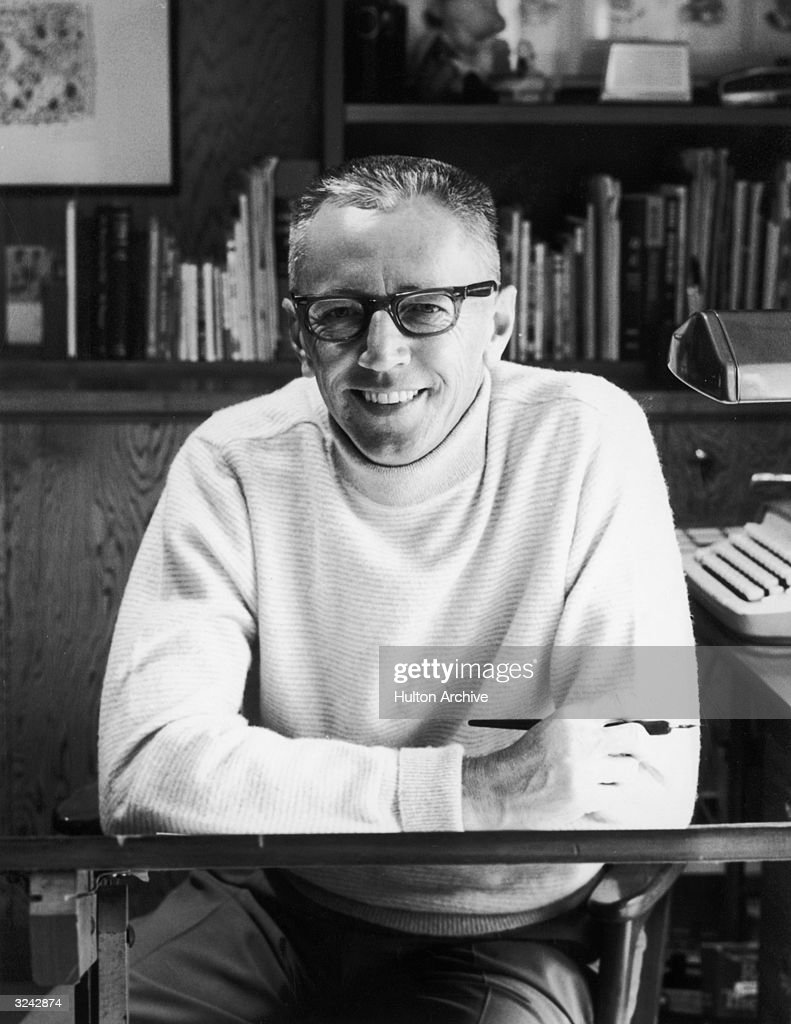 Portrait of American cartoonist Charles Schulz (1922 - 2000), creator of the Peanuts comic strip series, seated at his drawing table, pen in hand.