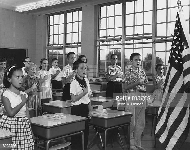 School children holding their hands over their hearts while reciting the Pledge of Allegiance in a classroom