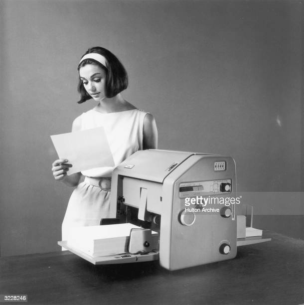 Studio image of a woman standing behind a mimeograph machine looking at a piece of paper