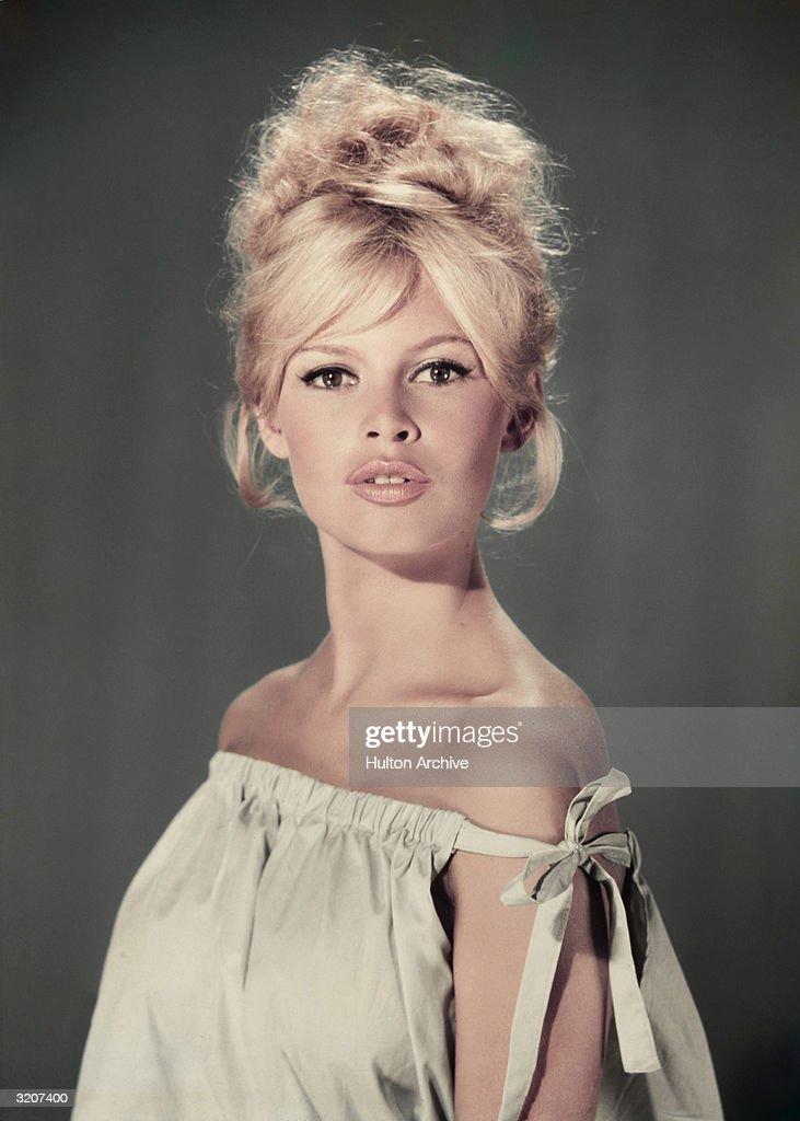 Studio portrait of actor and model Brigitte Bardot wearing a light blue offtheshoulder dress