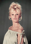 Studio portrait of actor and model Brigitte Bardot wearing a light blue offtheshoulder dress