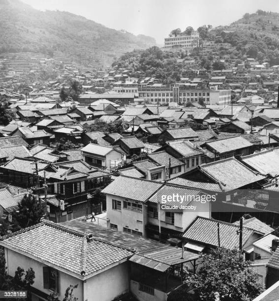 The postwar buildings in this district of Nagasaki were erected quickly of wood and cement blocks and bomb damage appears minimal despite the...