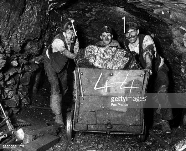 Three miners push a load of coal through the tunnel at Bromley pit in Pensford Surrey