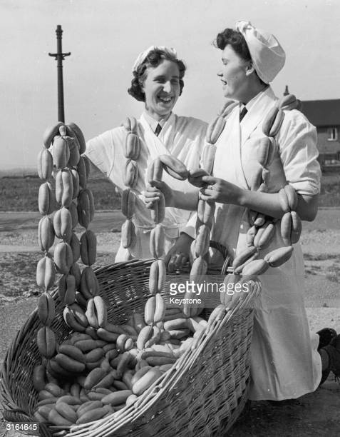 Two women selling strings of sausages from a huge basket