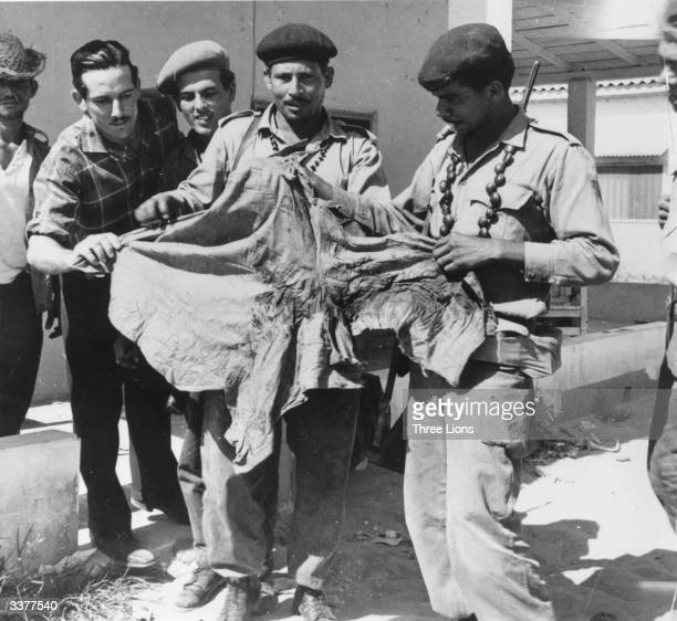 Castro's soldiers looking at a bloodstained shirt after the illfated 'Bay of Pigs' invasion at Playa de Giron Cuba